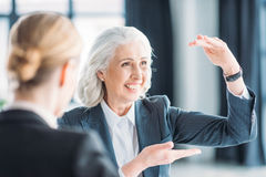 Senior businesswoman showing something to colleague on meeting Royalty Free Stock Photo