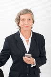 Senior businesswoman smile hold cellphone Royalty Free Stock Photos