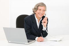Senior businesswoman smile sit behind office desk Stock Photo