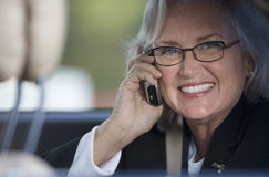 Senior businesswoman in spectacles using mobile phone, smiling, close-up, portrait Royalty Free Stock Images