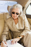 Senior businesswoman, in suit and sunglasses, sitting in back-seat of car, signing contract Stock Image