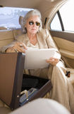 Senior businesswoman, in sunglasses, sitting in back-seat of car with open briefcase, holding document, portrait Royalty Free Stock Photography