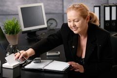 Senior businesswoman taking note. Smiling senior businesswoman taking note, looking at calendar sitting at office desk Stock Images