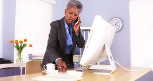 Senior businesswoman talking on phone and working in office Royalty Free Stock Images