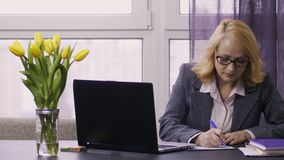Senior businesswoman typing on laptop at office. Portrait of good looking senior businesswoman sitting at desk in office, typing on laptop and taking notes stock video footage