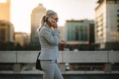 Senior businesswoman using cellphone on city street royalty free stock image