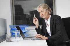Senior businesswoman using laptop and calculator at desk in office Royalty Free Stock Photo