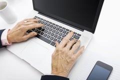 Senior businesswoman using laptop at office desk Stock Images
