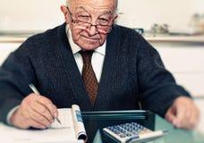 Senior calculate his expenses. Old caucasian man calculate his expenses Royalty Free Stock Photography