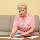 Senior calculating her debts and write it Royalty Free Stock Photos