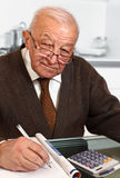 Senior with calculator Stock Images