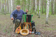 Senior camper is having rest in birch forest, sitting on a wicker stool and holding mandolin Stock Image