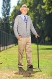 Senior with cane posing in a park Stock Image