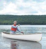 Senior canoe paddler. Elderly man paddling a white canoe stock image