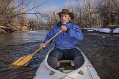 Senior canoe paddler. In a decked expedition canoe on the Cache la Poudre River, Fort Collins, Colorado, winter or early spring Royalty Free Stock Images