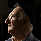 Senior in cap and eyeglasses sideview Stock Image