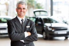 Senior car dealer principal. Confident senior car dealer principal standing in showroom Stock Image