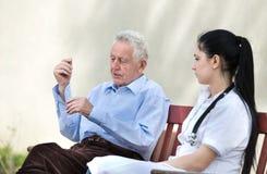 Senior care concept. Senior men talking to young nurse on the bench. Senior care concept Royalty Free Stock Photography