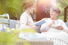 Senior and caregiver on terrace. Old women talking to a young caregiver reading a book during meeting on a terrace royalty free stock photography