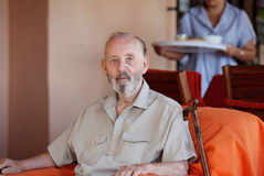 Senior with carer. Senior man in residential home with carer bringing meal Royalty Free Stock Image