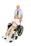 Senior Cares for Spouse. Senior man pushing his wife in wheelchair.  Full body isolated on white Stock Images