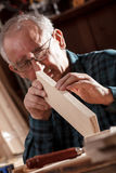 Senior carpenter checking sanded plank in his workshop Stock Photo