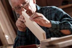 Senior carpenter checking sanded plank in his workshop Royalty Free Stock Image