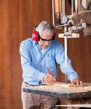 Senior Carpenter Cutting Wood With Bandsaw Stock Images