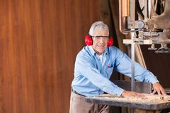 Senior Carpenter Cutting Wood With Bandsaw Royalty Free Stock Images
