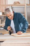 Senior Carpenter Cutting Wood With Saw In Workshop Royalty Free Stock Images