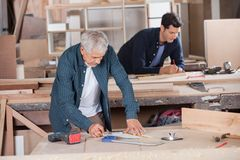 Senior Carpenter Drawing Diagram On Blueprint Stock Images