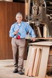 Senior Carpenter Holding Ear Protectors By Bandsaw Stock Image