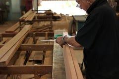 Senior carpenter measuring wooden plank in carpentry workshop. stock photos