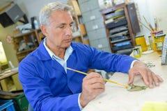 Senior carpenter planning work in workshop. Senior carpenter planning work in his workshop Stock Photos