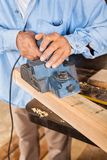 Senior Carpenter Shaving Wood With Electric Planer Royalty Free Stock Photo