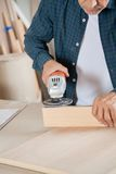 Senior Carpenter Using Electric Sander On Wood Stock Photos