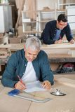 Senior Carpenter Working On Blueprint In Workshop Royalty Free Stock Photography
