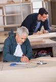 Senior Carpenter Working On Blueprint At Workshop Royalty Free Stock Image