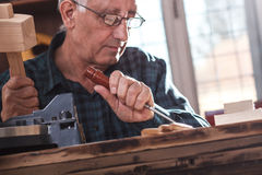 Senior carpenter working with tools. Closeup of a  senior carpenter working with a hammer, chisel and wood carving tools Royalty Free Stock Photo