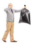 Senior carrying a stinky garbage bag Stock Photo