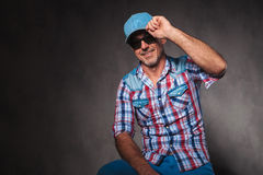 Senior casual man holding his hat in a greeting pose. Happy senior casual man holding his hat in a greeting pose, saying hello, in studio Stock Image