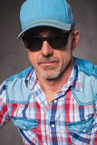 Senior casual man wearing baseball hat and sunglasses. Head and shoulders picture of a senior casual man wearing baseball hat and sunglasses, looking at the Royalty Free Stock Photo