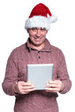 Senior casual man wearing santa hat is holding a pad tablet Royalty Free Stock Image