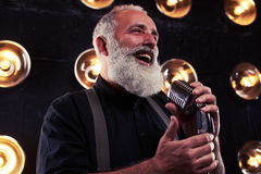 A senior Caucasian bearded man with microphone singing jazz. Close-up of a senior Caucasian bearded man with microphone singing jazz. Man rejoices coming while royalty free stock photo