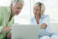 Senior couple using computer together at home royalty free stock images