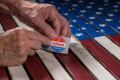 Roll of I Voted Today paper stickers on US Flag with hand removing one stock image