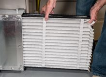 Senior man inserting a new air filter in a HVAC Furnace. Senior caucasian man changing a folded air filter in the HVAC furnace system in basement of home royalty free stock photo