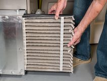 Senior man changing a dirty air filter in a HVAC Furnace. Senior caucasian man changing a folded dirty air filter in the HVAC furnace system in basement of home royalty free stock photos