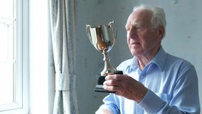 Senior man cleaning his trophy