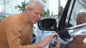 Senior man examines car wing at the dealership. Senior caucasian man examining car wing at the dealeship. Low shot of aged male customer touching surface of the Stock Image